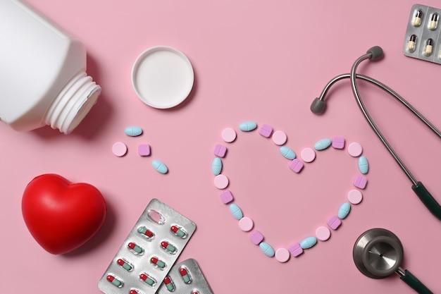 Pigułki medyczne, czerwone serce i stetoskop na różowym tle. koncepcja ubezpieczenia zdrowotnego.
