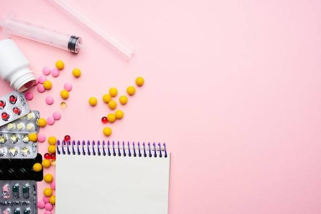 Pigułki notatnik strzykawka materiały medyczne różowe tło