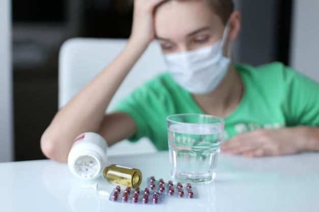 Pigułki od przeziębienia na białym stole i zdenerwowany chłopak w domu. koronawirus