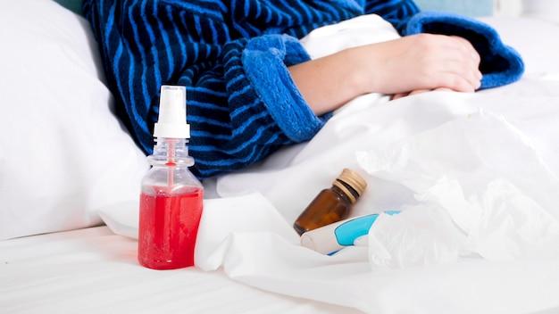 Pigułki, spray i leki leżące w łóżku z chorą młodą kobietą.