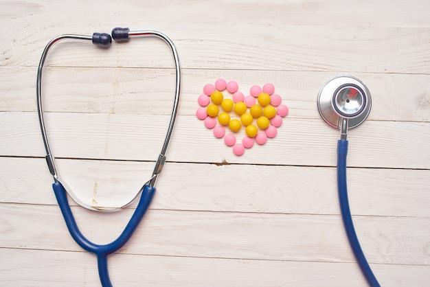 Pigułki stetoskop drewniane tło leczenie szpital