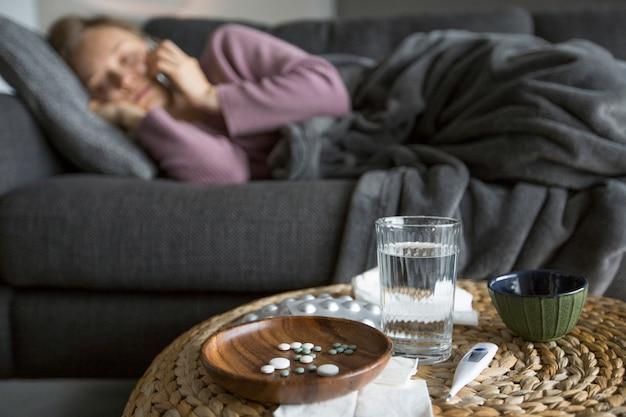 Pigułki, szklanka wody, termometr na stolik do kawy na ostrości