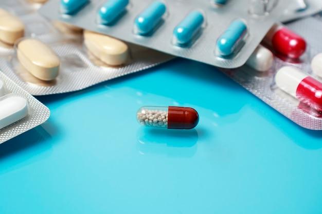Pigułki, tabletki lub kapsułki na jasnoniebieskim medycznym tle odbijającym. medycyna, zdrowie, leczenie, koncepcja farmacji. wykształcenie medyczne.