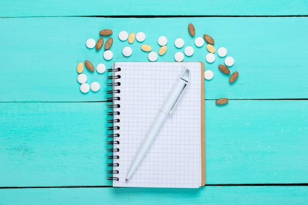 Pigułki z notatnikiem na niebieskim drewnianym.