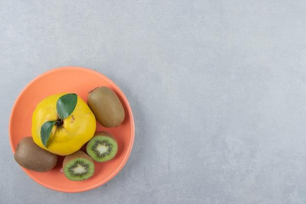 Pigwa i pokrojone kiwi na pomarańczowym talerzu.