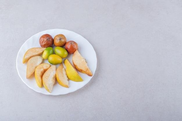 Pigwa, nieszpułki i kumkwaty na talerzu na marmurowym stole.