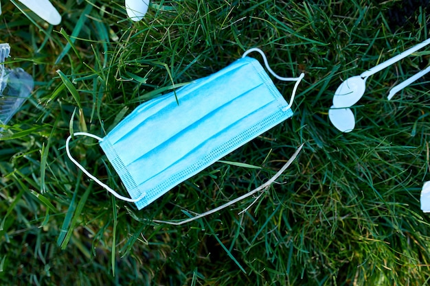 Piile porozrzucanych śmieci na tle zielonej trawy
