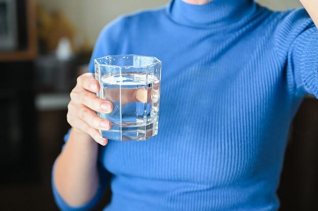 Pij dużo wody z wirusa, pandemicznego koronawirusa covid-19. młoda kobieta pije wodę ze szklanki