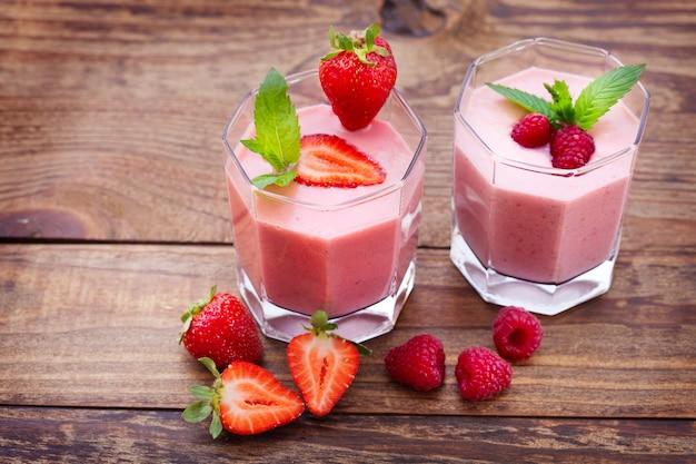 Pij koktajle letnie truskawki, jeżyny, maliny na drewnianym stole.