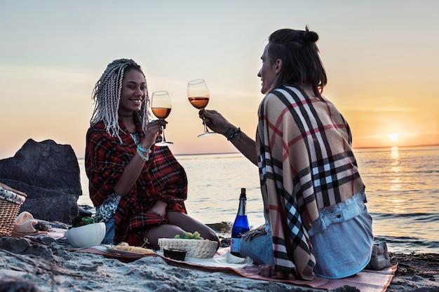 Pij szampana. promieniejąca kobieta z dredami pije szampana z mężczyzną na pikniku