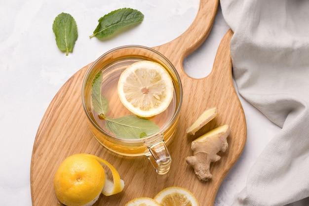 Pij z cytryną, imbirem i miętą na drewnianej desce do krojenia