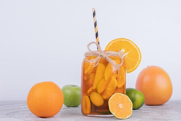 Pij z grejpfrutem, limonką i cynamonem na białym tle.