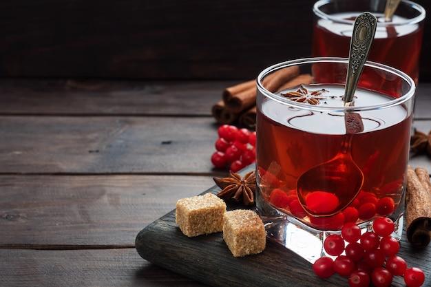 Pij z jagód czerwonej kaliny w szklanym kubku.