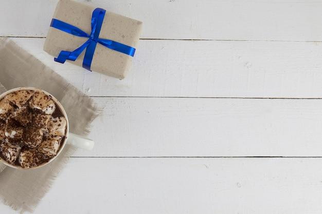 Pij z piankami na drewnianej powierzchni i prezent