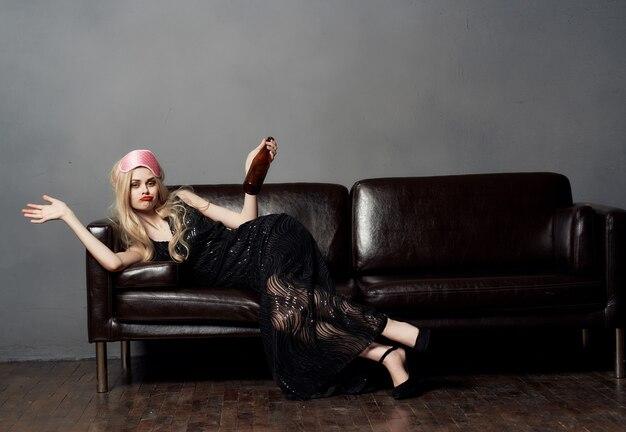 Pijana kobieta z butelką alkoholu leży na zamazanych ustach na kanapie