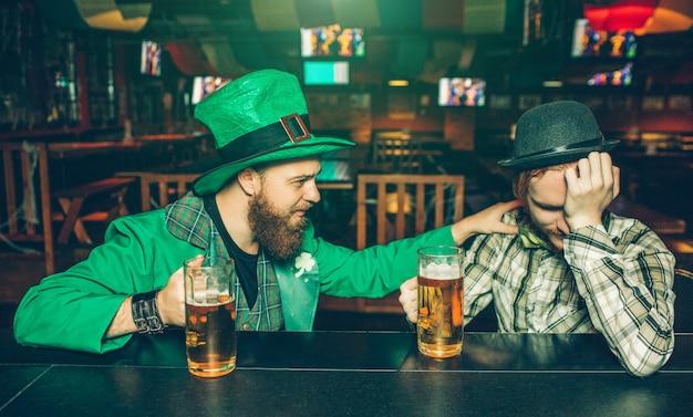Pijani młodzi ludzie siedzą przy barze w pubie. facet w zielonym garniturze dotyka swojego przyjaciela. młody mężczyzna po lewej ma kaca. mają kufle piwa.