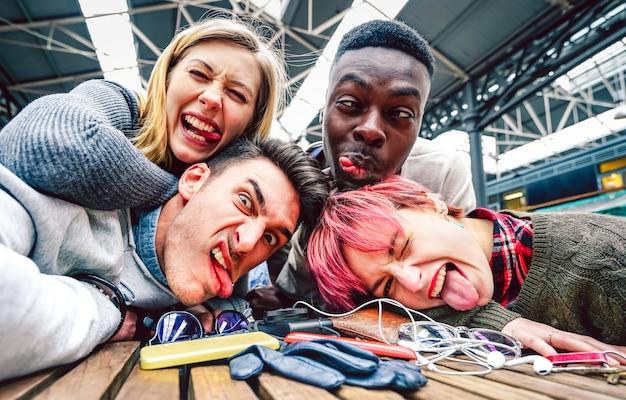Pijani przyjaciele robią selfie z szalonymi śmiesznymi twarzami na imprezie w pomieszczeniach