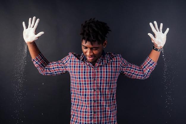 Pijany afroamerykanin afro biznesmen niechlujny mężczyzna z dredami ręce do góry zabrudzone białym proszkiem kurz chemiczny narkotyk aresztowanie policji kuba na czarnym tle w studio.poddaje się policji