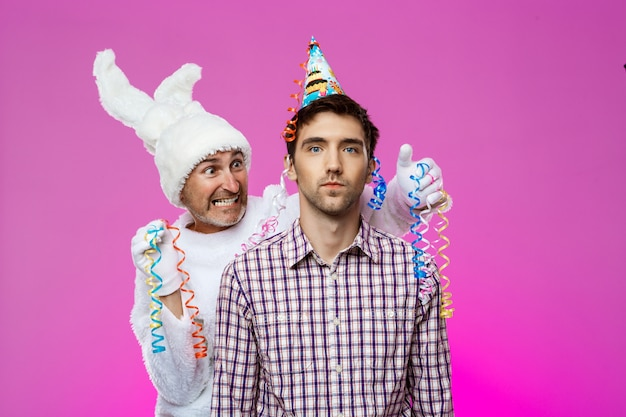 Pijany mężczyzna i królik na przyjęciu urodzinowym na ścianie fioletowy.