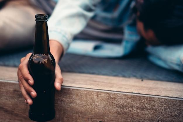 Pijany mężczyzna trzyma butelkę piwa