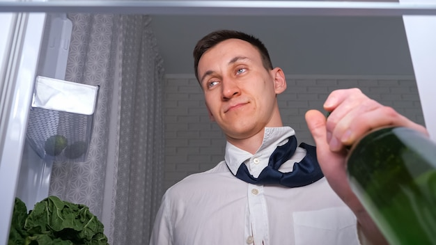 Pijany mężczyzna w białej koszuli i krawacie otwiera drzwi, aby zabrać butelkę zimnego piwa z półki w ciemnej kuchni, zamknij widok z wnętrza nowej lodówki