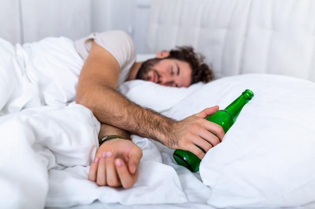 Pijany mężczyzna w łóżku i smutne miejsce oraz butelka alkoholu w ręku. młody człowiek leżący w łóżku śmiertelnie pijany, trzymając prawie pustą butelkę wódki.