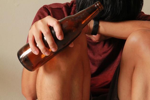 Pijany mężczyzna z butelką piwa ma stres w życiu i siedzi samotnie w pustym pokoju, smutny, samotny, szkoła, wiek dojrzewania, przemoc domowa, niechciane problemy miłosne, sam, rodzina