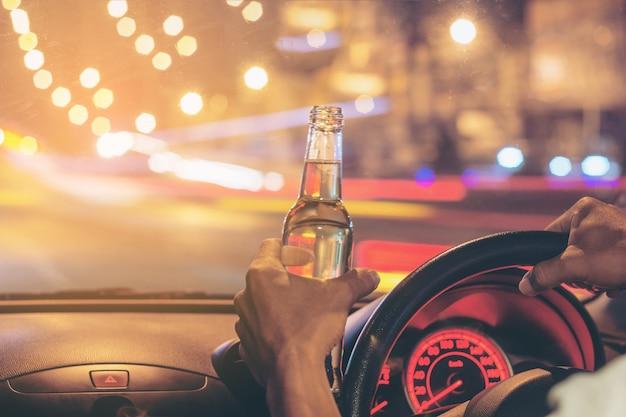 Pijany młody człowiek jeździ samochodem z butelką piwa.