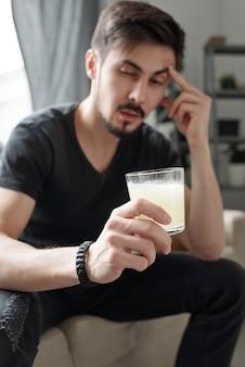 Pijany młody człowiek odczuwa ból głowy rano po przyjęciu, pijąc pigułkę rozpuszczoną w wodzie podczas leczenia kaca