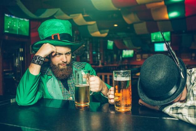 Pijany młody człowiek w zielonym garniturze siedzieć przy barze w pubie z przyjacielem. kolejny facet zasnął. mają kufle piwa.