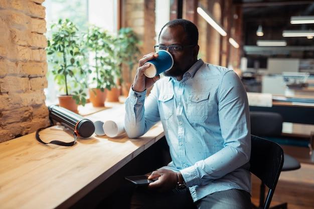 Piję kawę. ciemnoskóry dojrzały projektant wnętrz pijący kawę siedzącą przy oknie