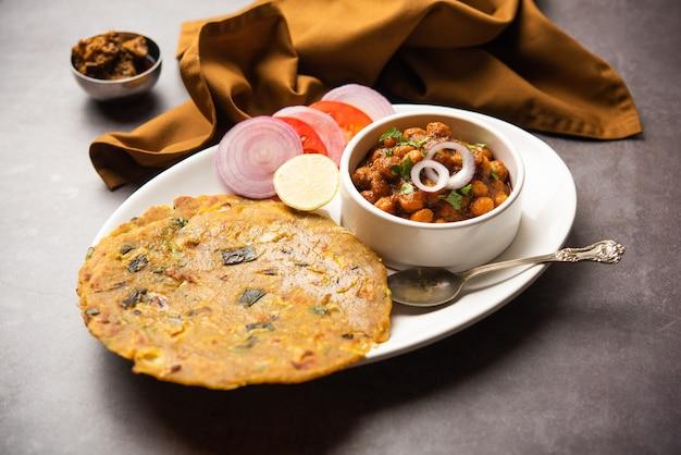 Pikantna ciecierzyca masala lub chole curry z pyaj paratha lub spring onion parantha i piklowane mango