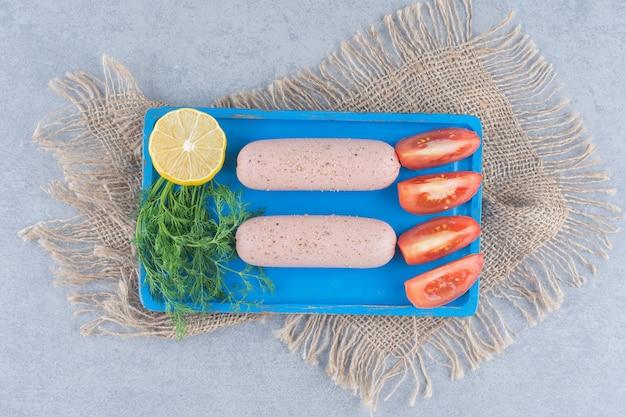 Pikantna kiełbasa gotowana z warzywami na niebieskiej desce.