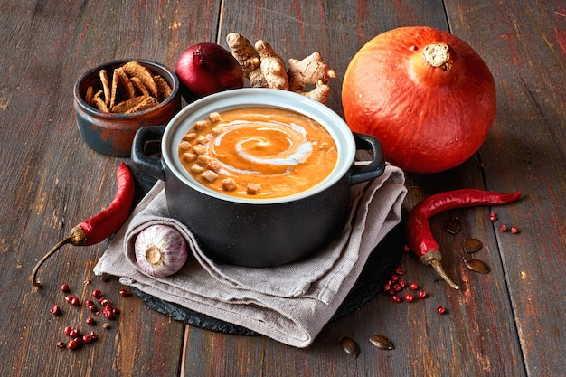 Pikantna kremowa zupa dyniowa z imbirem, hiszpańską cebulą, czosnkiem i chili w ceramicznej patelni na ciemnym drewnie