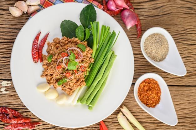 Pikantna mielona sałatka wieprzowa na białym talerzu z czerwoną cebulą, trawą cytrynową, czosnkiem, długimi fasolami, liśćmi limonki kaffir i szczypiorkiem