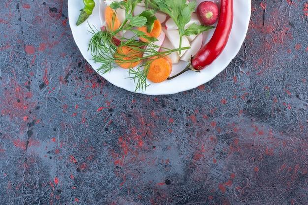Pikantna mieszanka warzyw na białym talerzu na czarnym stole.