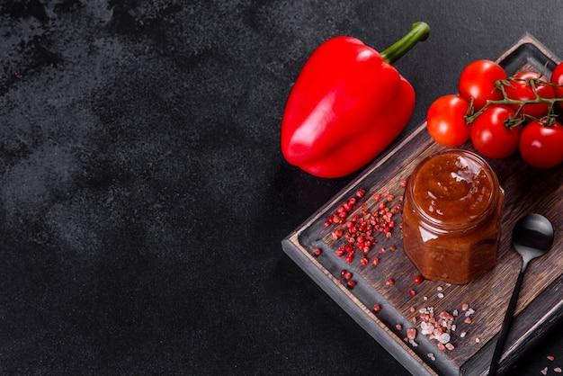 Pikantna przyprawa adżika kuchni gruzińskiej w misce z czerwoną papryką i czosnkiem na betonowym stole z bliska