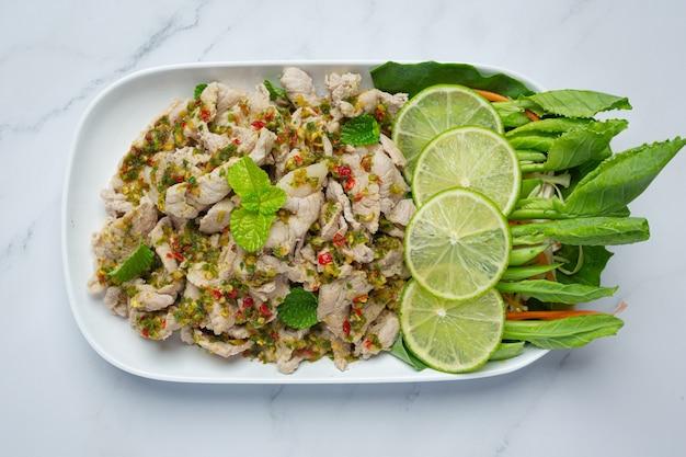 Pikantna sałatka wieprzowa podawana ze świeżymi, chrupiącymi łodygami jarmużu tajskie jedzenie.