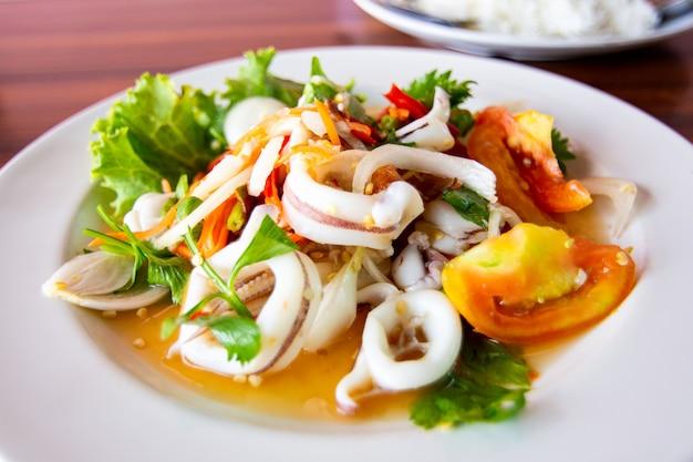 Pikantna sałatka z kalmarów z pomidorami i mieszanką warzyw.