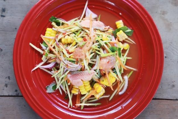 Pikantna sałatka z łososia w czerwonym naczyniu i na drewnianym stole, tajskie jedzenie warzywno-ryba łosoś dobre jedzenie dla zdrowego tajskiego call yum (sałatka i pikantna)