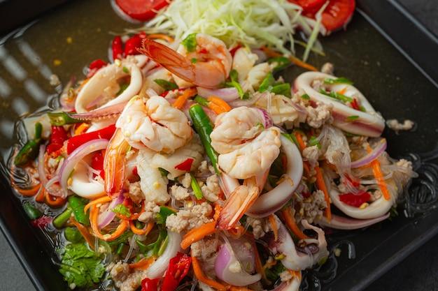 Pikantna sałatka z mieszanych owoców morza z tajskimi składnikami żywności.