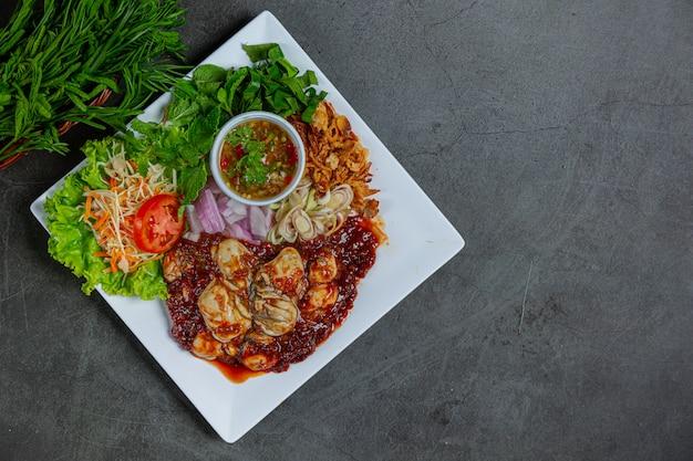 Pikantna sałatka ze świeżych ostryg i tajskie składniki żywności.