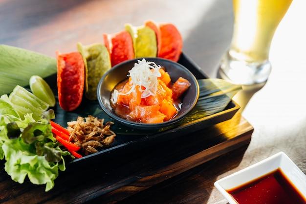 Pikantna surowa sałatka z łososia podawana z chrupiącymi czerwonymi i zielonymi chipsami na canape i zimne piwo.