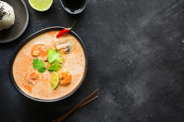 Pikantna tajska zupa tom yam kung z krewetkami, owocami morza, mlekiem kokosowym, papryczką chili i ryżem.