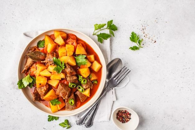 Pikantna wołowina duszona z ziemniakami w sosie pomidorowym w białym talerzu, widok z góry.