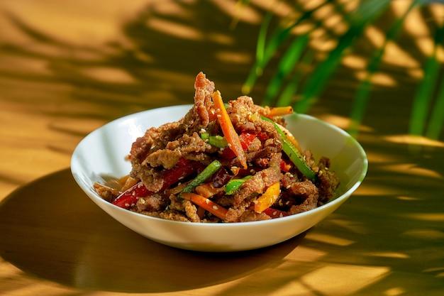 Pikantna wytrawna wołowina z syczuańskiego woka z papryką, sezamem, marchewką i zielonym pomidorem w białej misce. chiński kuzyn