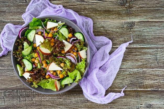 Pikantna zdrowa sałatka ze świeżych warzyw, czerwonej cebuli, ciecierzycy, wędzonego sera (ser kiełbasowy), ogórków w misce na drewnianym stole. danie wegetariańskie. widok z góry.