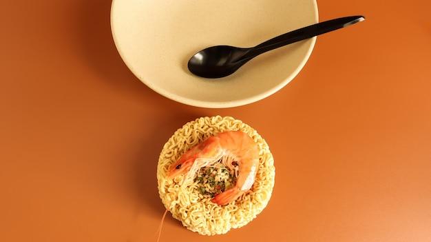 Pikantna zupa błyskawiczna z makaronem z krewetkami. zupa z krewetek, gotowanie, jedzenie. surowy suszony makaron w kształcie koła w talerzu. azjatyckie jedzenie. makaron, do przygotowania którego wystarczy zalać wrzątkiem.