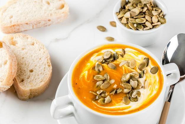 Pikantna zupa dyniowa z pestkami dyni, śmietaną i świeżo upieczoną bagietką na czarnym kamiennym stole
