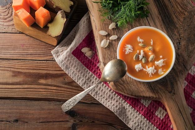 Pikantna zupa krem z dyni z serem i nasionami na drewnianym stole na obrusie w czerwoną kratkę.